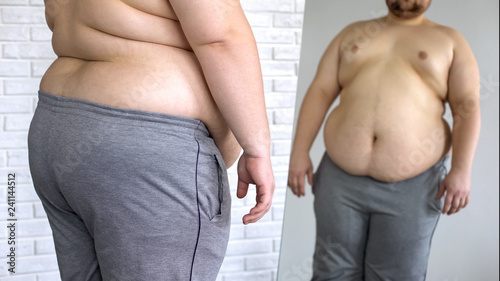 Foto Sad overweight man looking at fat belly mirror reflection, weight loss problem