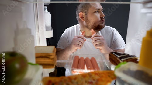 Fotomural Addicted man secretly eating sausages at night near fridge, unhealthy nutrition