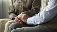 Elderly Couple Sitting On Sofa, Holding Hands, Understanding In Long Marriage