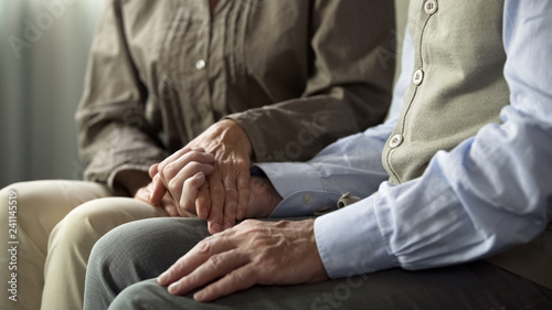 Valokuva  Retiree male and female sitting on sofa, woman holding man hand support and care