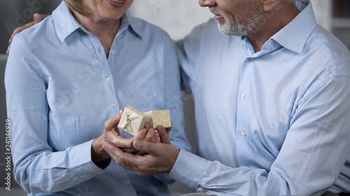 Photo  Senior husband giving present to wife, woman delighted with precious gift