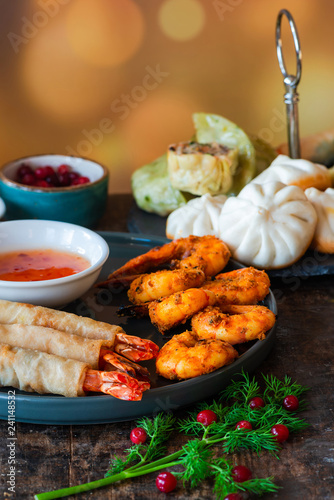 Giant king prawns and selection of mini Chinese dumplings with sweet chili dipping sauce. Party food idea.