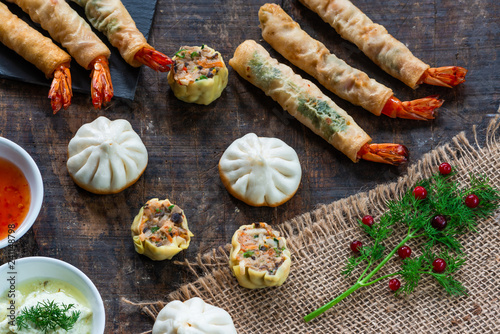 Giant king prawns and selection of mini Chinese dumplings with sweet chili and yogurt dipping sauces. Party food idea. Top view.