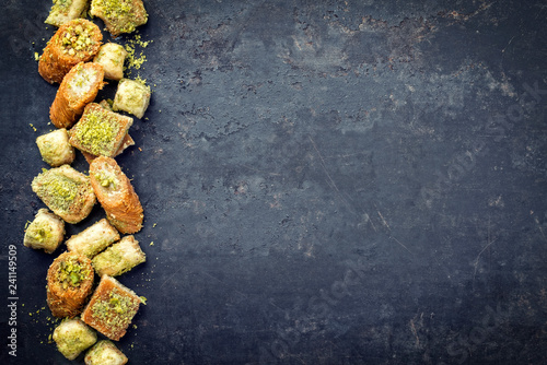 Traditional Oriental baklava collection as top view on a black board with copy s Wallpaper Mural