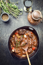 Traditional German Braised Pork Cheeks In Brown Sauce With Mushroom And Carrots As Top View In A Cast-iron Pot