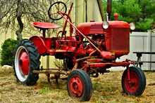 A Red Light Duty Farm Tractor Sits Idle