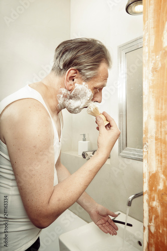 Fotografía  Aging man in a-shirt shaving face with old style razor