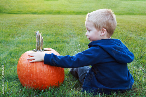 Fotografie, Obraz  Young child holding his new pumpkin for Halloween in a grassy field