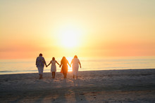 Happy Loving Family Holding Hands And Embracing While Facing The Bright Orange Yellow Sunset Over The Ocean At The Florida Beach Horizon