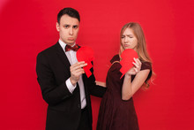 Photo Of A Young Couple, Man And Woman, Isolated On A Red Background, Holding A Broken Heart.