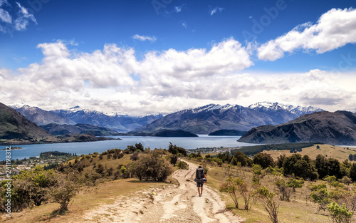 Fotografie, Obraz  A lonely hiker with a big backpack explores the hill of Wanaka, New Zealand