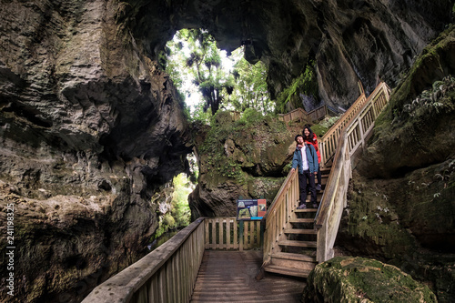 Young happy couple explores amazing rock formation in Waikato, New Zealand. Happiness image of travelers visiting the natural landscape. Romantic image of young people in cave.