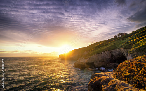 Foto auf Leinwand Lavendel An epic sunset with dramatic burning clouds in Tunnel Beach of Dunedin, New Zealand. One can enjoy ocean view, cliff, rolling hills, sunset, coves, rock formation in this famous tourist attraction.