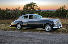 Classic Luxury Car On Rural Road At Sunset