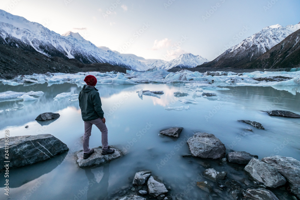 Fototapety, obrazy: A traveler viewing the amazing icebergs and snow mountains during dusk in Mount Cook, New Zealand. This place is famous among tourists, backpackers, hikers and locals. The scenery is beautiful.