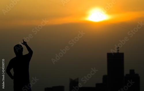 Fotografía  An unidentified man points into the sun