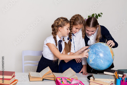 Fotografia  three girls schoolgirls on the lesson of geography with a globe in school