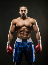 Muscular African American Black Male Sweaty Boxer Stands Menecenly Facing  Towards The Camera  With Dramatic Lighting With A Black Background