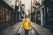 Leinwanddruck Bild - A rear view of a girl in a yellow coat walking along the historic street known as The Shambles in York, UK which is a popular tourist destination and medieval landmark in this ancient city