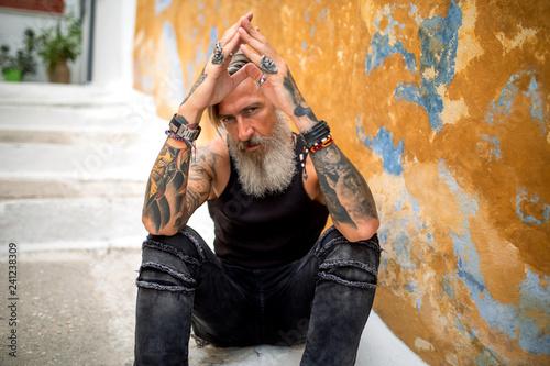 Porträt eines sitzenden, nachdenklichen, bärtigen Mannes vor einer Hauswand Canvas Print
