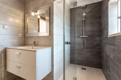 Fotografia Modern bathroom with shower and washbasin for hygiene.