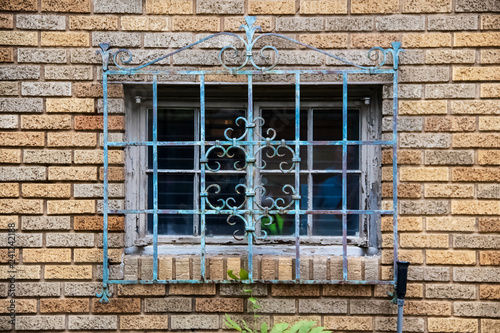 Foto  Ornate metal grill with gungy paint over an old window in a brick building - clo