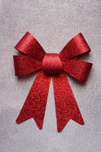A Beautiful Big Red Bow On A Silver Glittering Background.Detail Of A Red Glittering Bow On A Gift Wrapped In Silver Wrapping Paper.Concept For Felicitation Or Gift Bag.