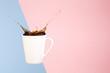 Leinwanddruck Bild - Coffee concept. Minimal art. Solid background. Coffee splashes. Levitating mug