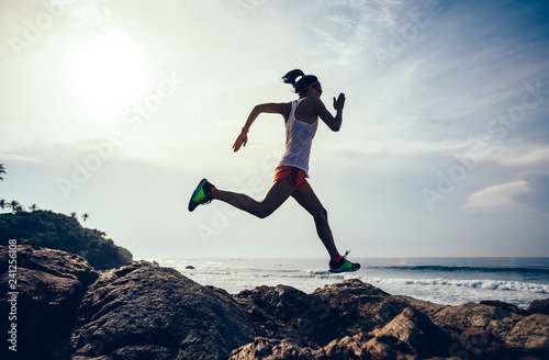 Poster Glisse hiver Young fitness woman trail runner running to rocky mountain top on seaside