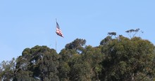 American Flag Ragged Above Trees Old Historic San Diego. Old Town San Diego State Historic Park. Historical Building, Display And Education. School House, Newspaper Office, Stage Coach, Flag, Etc.