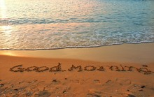 The Word Of Good Morning Writing On Sand Beach With Waves Blue Ocean.