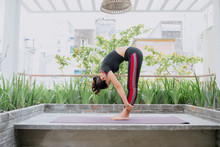 Young Asian Woman In Relaxation Stretching Position On Her Balcony Floor