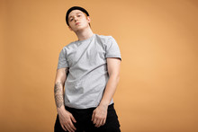 Cocky Stylish Guy Dressed In A Gray Shirt, Black Jeans And Black Hat With Tattoo On His Hand Is Standing On The Beige Background In The Studio