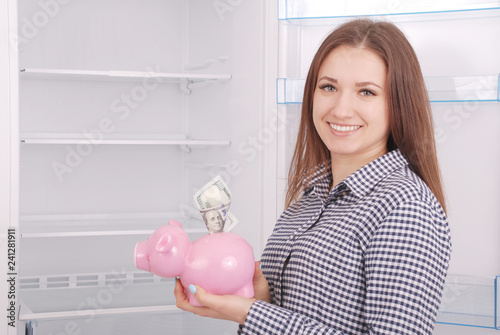 Photo  Young beautiful woman standing with piggy bank (money box)