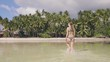Beautiful woman walking on sea water at tropical island after bathing at summer day. Young woman in swimsuit in ocean beach and tropical palm tree on shore. Happy girl on paradise beach.