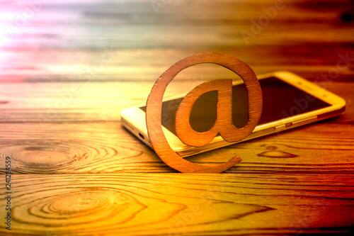 smartphone, sign the e-mail on a wooden background. Internet, world wide web, communication, correspondence.