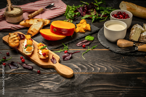 Aluminium Prints Picnic gourmet Italian snack. crostini with ricotta, mango, cranberry on a dark wooden background. Flat top view. copy space