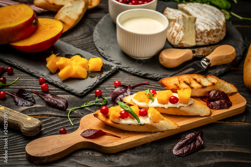 Aluminium Prints Picnic sandwiches with ricotta, mango, cranberry on a dark wooden background, Flat top view. copy space. Restaurant meals, gourmet Italian snack, food photo, menu concept