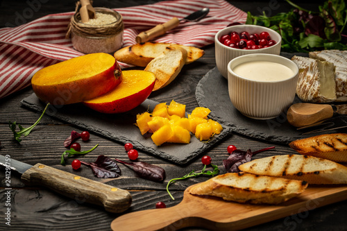 Aluminium Prints Picnic Ingredients for sandwiches with ricotta, mango, cranberry on a dark wooden background, Flat top view. copy space