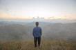 rear of happy man stand on top mountain looking view with mist and cloud at Doi Langka Luang, Chiang Rai province. soft focus.
