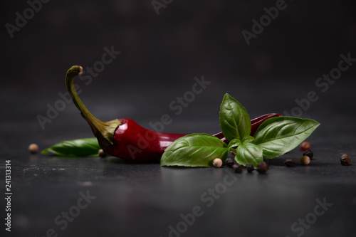 chili peppers with basil and peppercorns on a rustic surface Wallpaper Mural