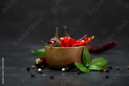 Fotografía chili peppers with basil and peppercorns in bowls on a rustic surface,