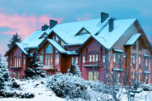 Luxurious Log House, Wooden Mansion Covered By Snow In Winter Park At Sunset Time.