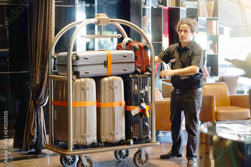 Fotografía Close-up many suitcases on hotel luggage cart moving by bell boy