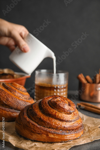 Parchment with freshly baked cinnamon rolls on table