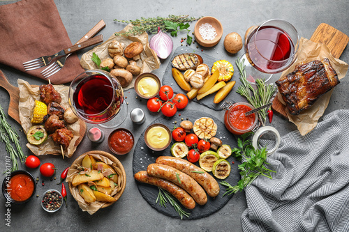 Delicious meal served for barbecue party on gray table, flat lay