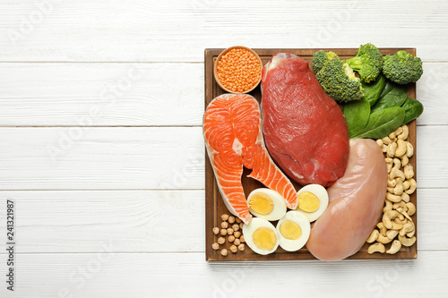 Set of natural food high in protein and space for text on wooden background, top view