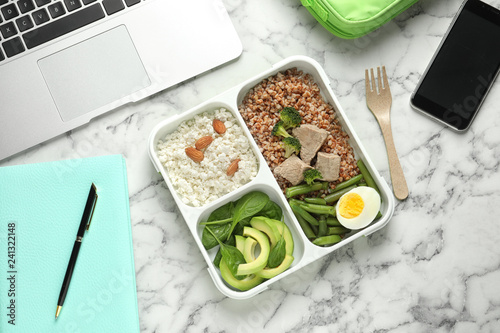 Flat lay composition with container of natural protein food on office table