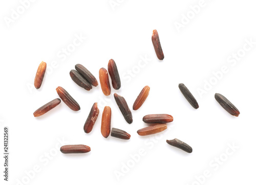 Scattered grains of brown rice on white background, top view