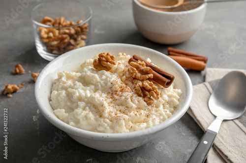 Poster Graine, aromate Creamy rice pudding with cinnamon and walnuts in bowl served on grey table